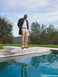 A black man in a dress shirt and slacks with a long leather coat is standing on a diving board at a swimming pool. The man has his hands in his pockets. The man is looking down at the pool and watching his reflection in the water.